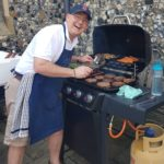 Dr. O grills for neighbors at his church's community day